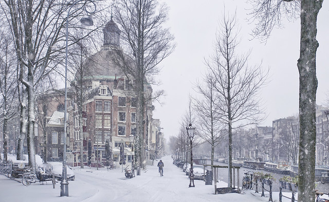 A lonely cyclist goes through the snow and passes the Koepelkerk in Amsterdam.