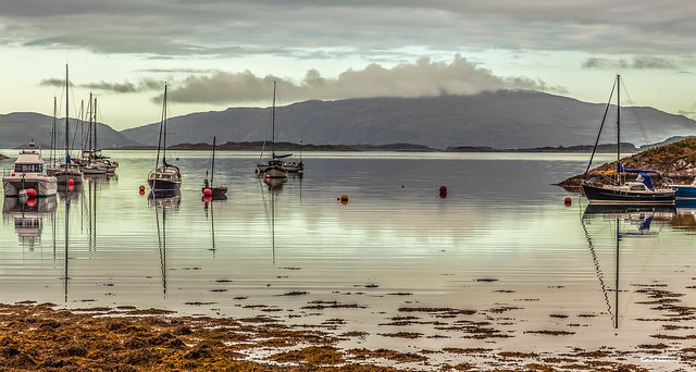 Soft light of dawn breaking through the clouds from Crinan Bay. Low islands of Garbh Reisa are a natural break-water. Cloud over Scarba is like a simmering volcano. One headland of Jura, far left and pure tranquillity.