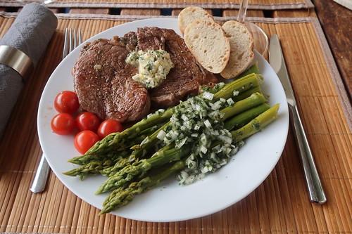 Gegrillte Entrecôtes mit Kräuterbutter, Spargelsalat, kleinen Tomaten und Baguette