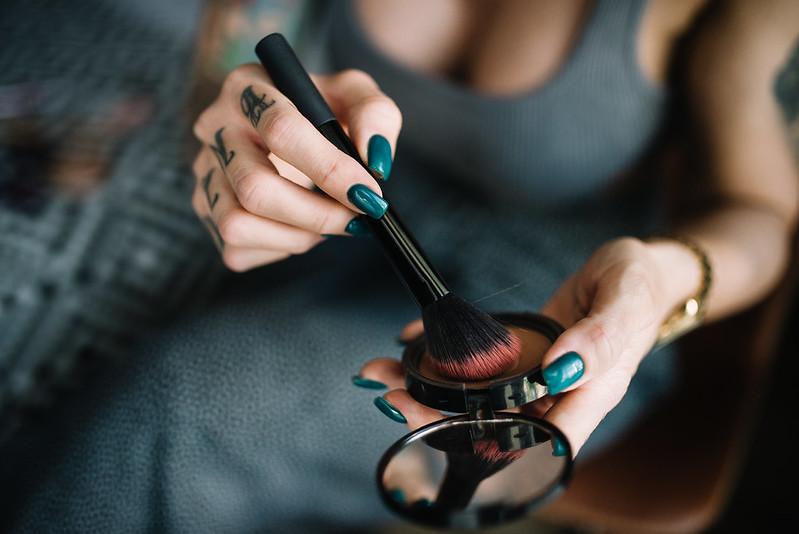 Makeup artist with blush and brush closeup.