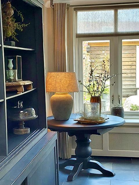 Ronde klassieke tafel kruiklamp windlicht in houten schaal grijze buffetkast stolp bajot tafeltje