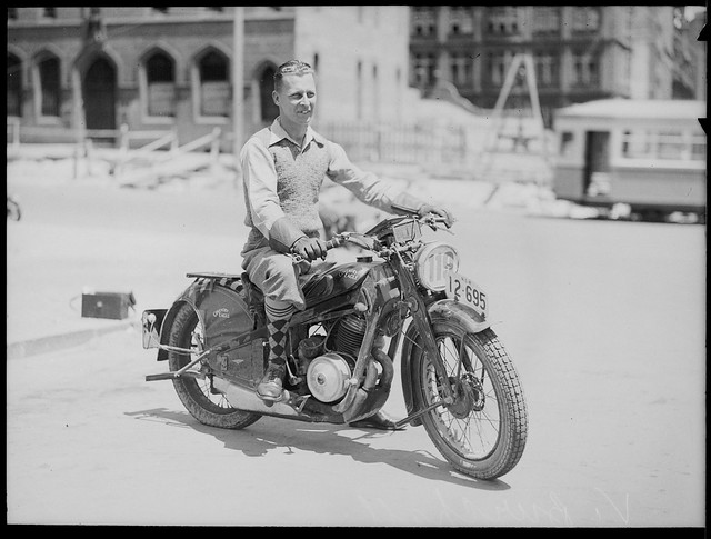 Motorcycle rider posing with a Coventry Eagle racing bike, No. 116, city street setting, ca. 1935