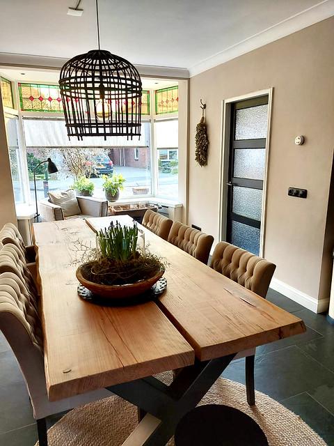 Woonkamer met glas-in-lood erker kooilamp kruispoot tafel