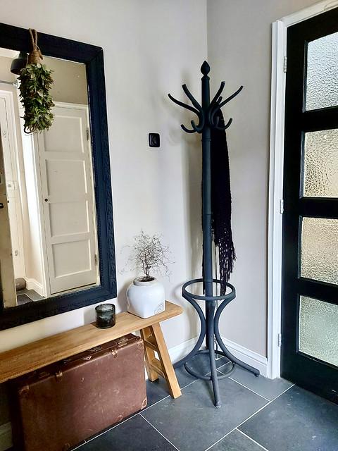 Zwarte spiegel zwarte kapstok zwarte binnendeur bankje hal