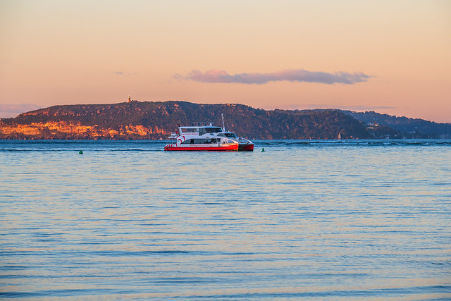 Sunrise at the channel with ferry and headland in the distance