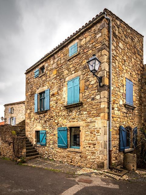 La maison en arkose et aux volets bleus