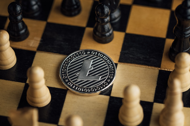 Litecoin physical coin surrounded by chess pieces