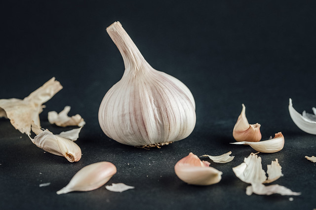 Garlic cloves around a whole garlic head on black background