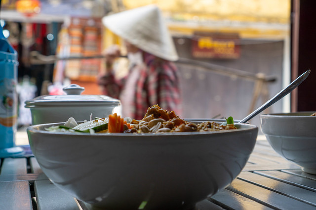 Food Photo of Bowl of Vietnamese Bun Thit Nuong with Vietnamese Woman with Conical Hat and Shoulder Pole in the Background in Hoi An, Vietnam