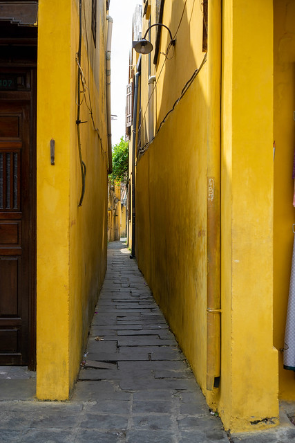Narrow Alleyway in between two Yellow Buildings in the Ancient Town of Hoi An, Vietnam