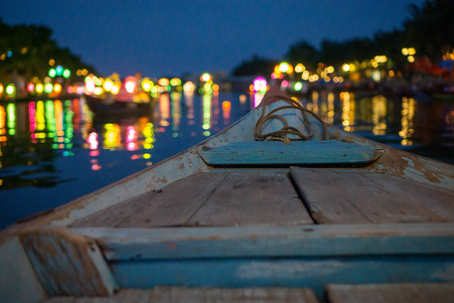 Night Photo from a Wooden Tourist Boat with Bright Lights reflecting in Thu Bon River in Hoi An, Vietnam