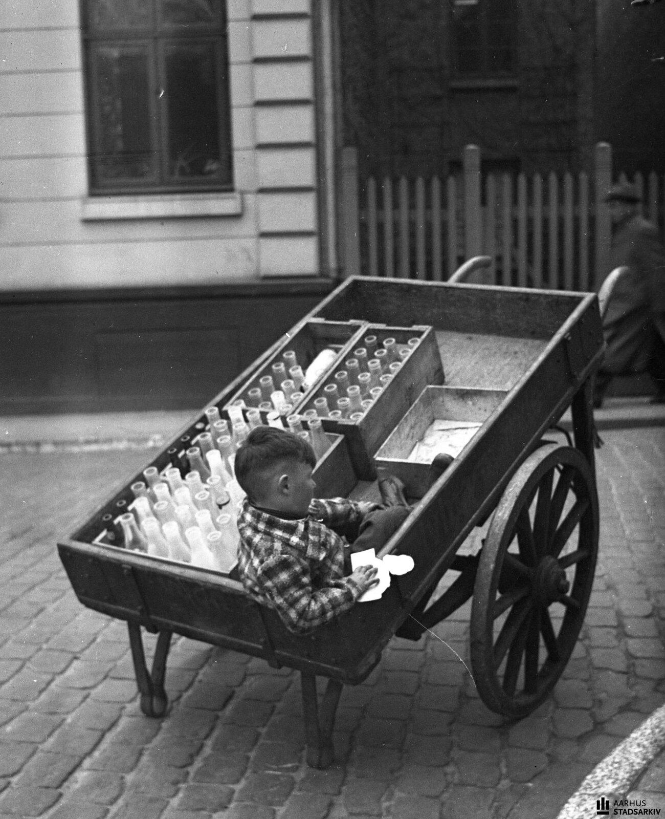 1943. Мальчик сидит в тележке с молочными бутылками