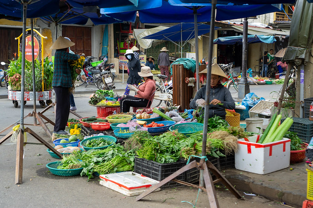 Vietnamese Women selling Herbs, Fruits and Vegetables at a Street Market at the Entrance of the Walking Street in Hoi An, Vietnam