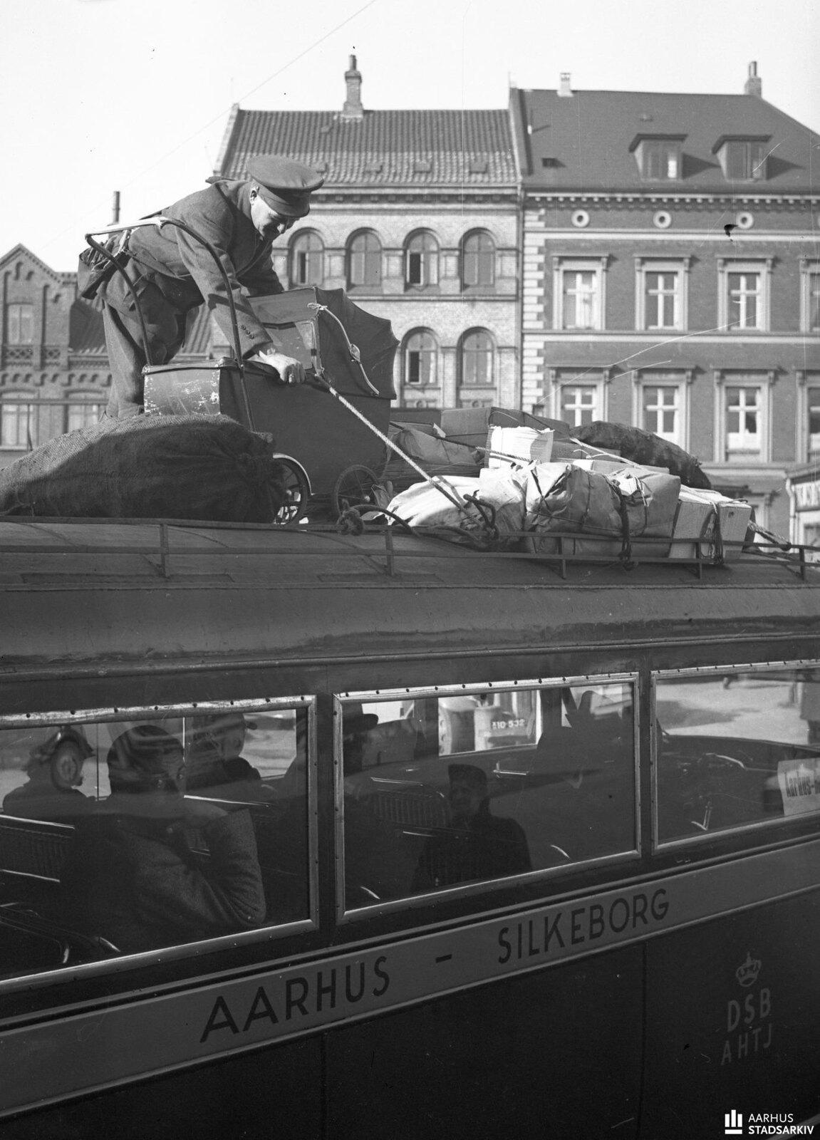 1943. Водитель Альфред Кристенсен загружает багаж на крышу автобуса