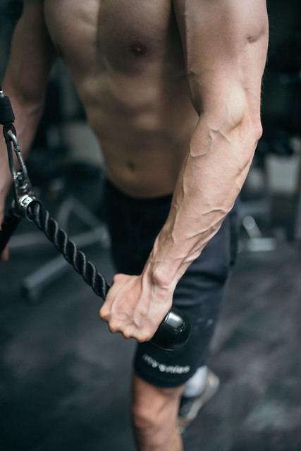 Attractive man working on cross machine in the gym. Arm closeup.