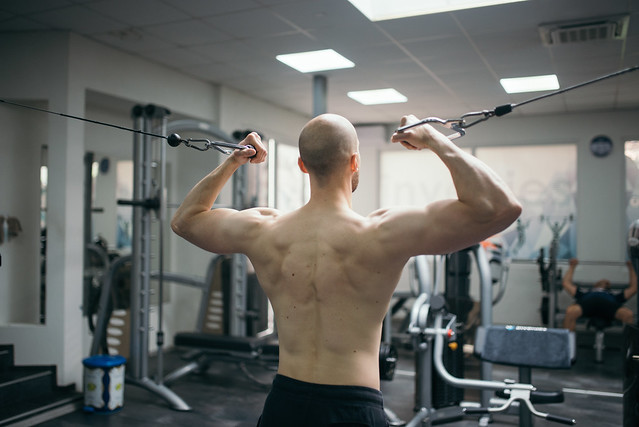 Handsome sportsman doing chest exercise with machine. Back view.