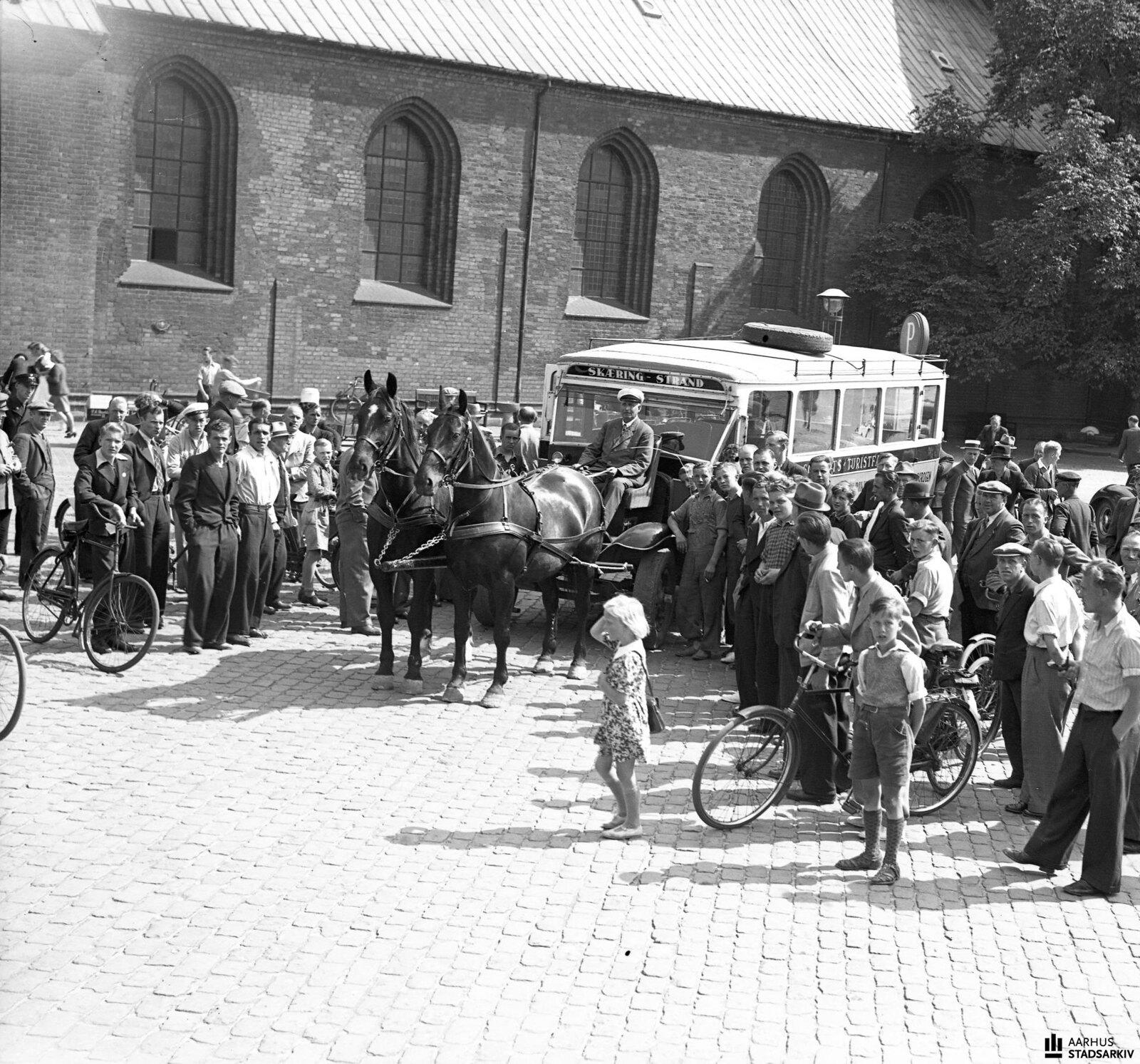 1940. Толпа вокруг автобуса с двумя привязанными лошадьми. Переоборудованный автобус, который использовался для движения по маршруту Орхус-Скуринг, принадлежит ресторатору Ингеману Шмидту,