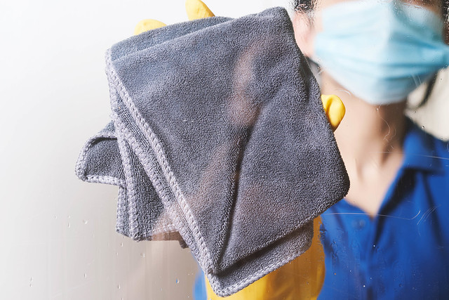 A housewife in face mask wiping window glass