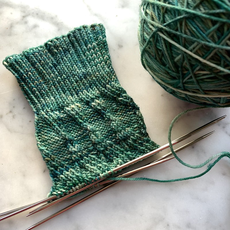 Pair of green socks in progress, on double-pointed needles, next to a ball of yarn, on a marble tabletop