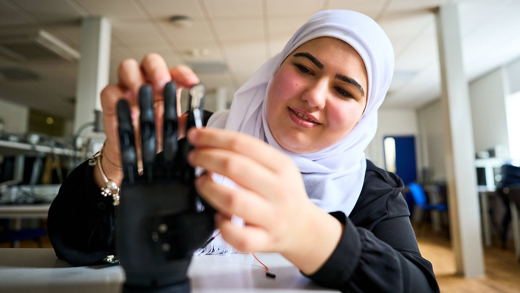 Leen attaches a sensor to a prosthetic hand in an electronic engineering lab.