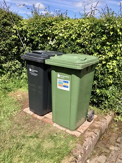 A photo of two wheelie bins stood on top of a small area of bricks set into a small lawn
