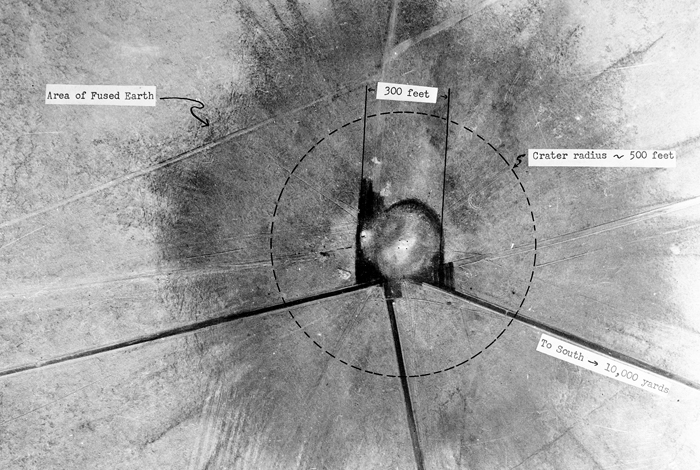 An aerial view of ground zero 28 hours after the Trinity Test on July 16, 1945. The nuclear blast created a newly discovered quasicrystal that was formed in the fusion of surrounding sand, the test tower, and copper transmission lines.