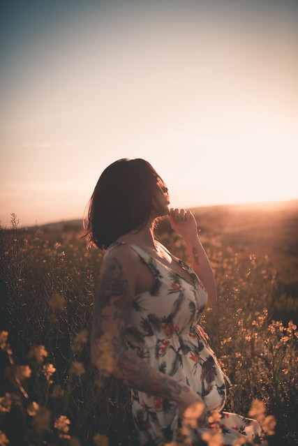 A tattooed woman enjoys the sunset.