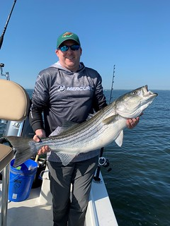 This happy angler was lucky enough to catch a nice 42-inch striped bass recently. Photo by John Atchison