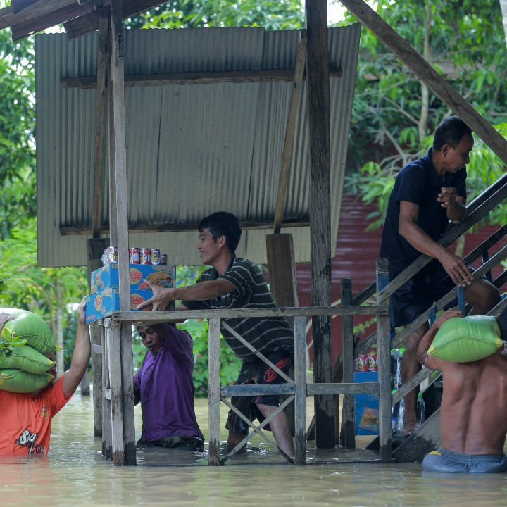 Men carrying food and supplies through flood water, before taking them up some stairs to store