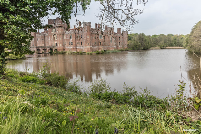Herstmonceux Castle and its lake-like moat seen from the south-east, East Sussex, England.