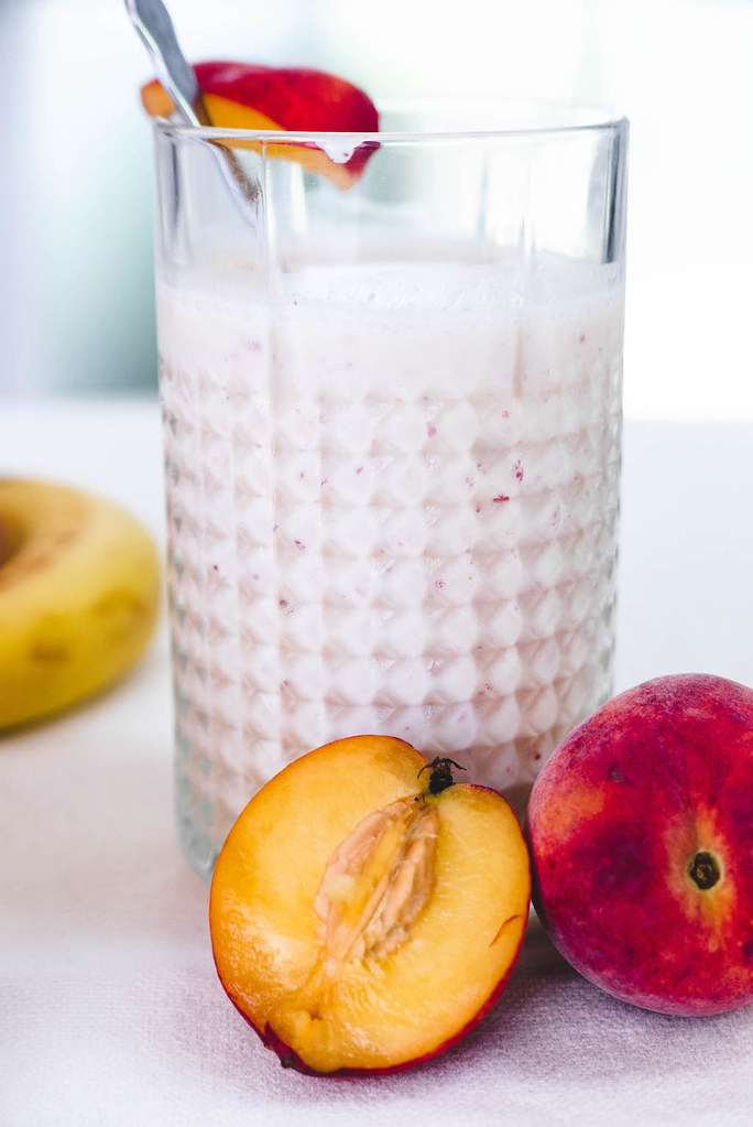 A large smoothie next to peaches.