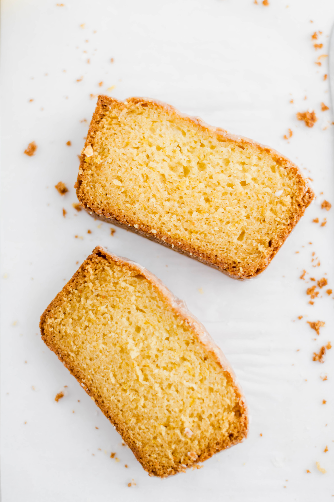 Two slices of starbucks lemon loaf with crumbs surrounding them on a white backdrop.