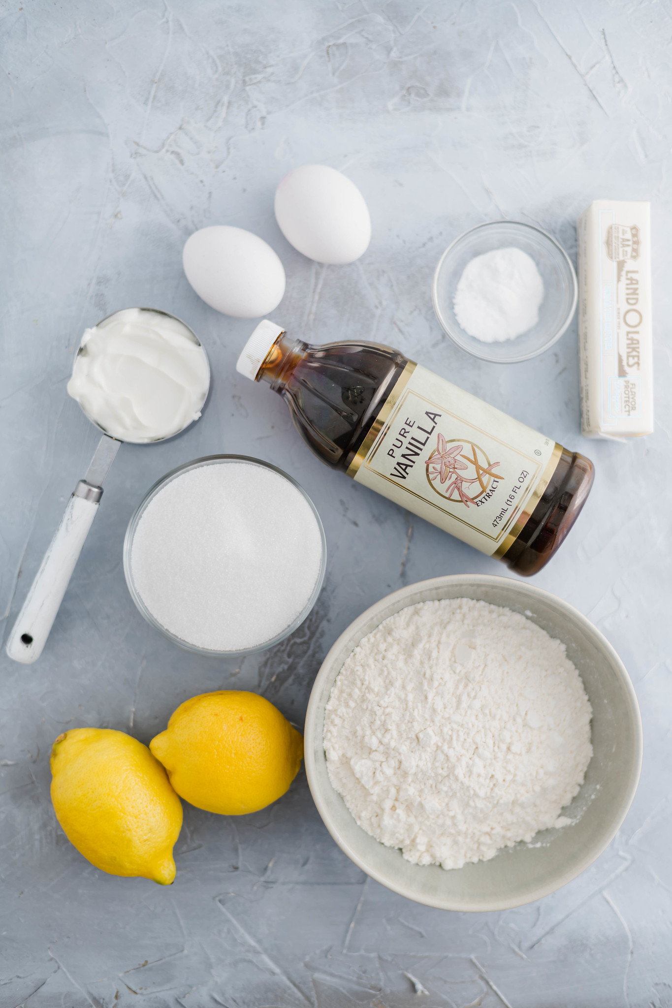 Required ingredients for starbucks lemon loaf arranged on a gray backdrop.
