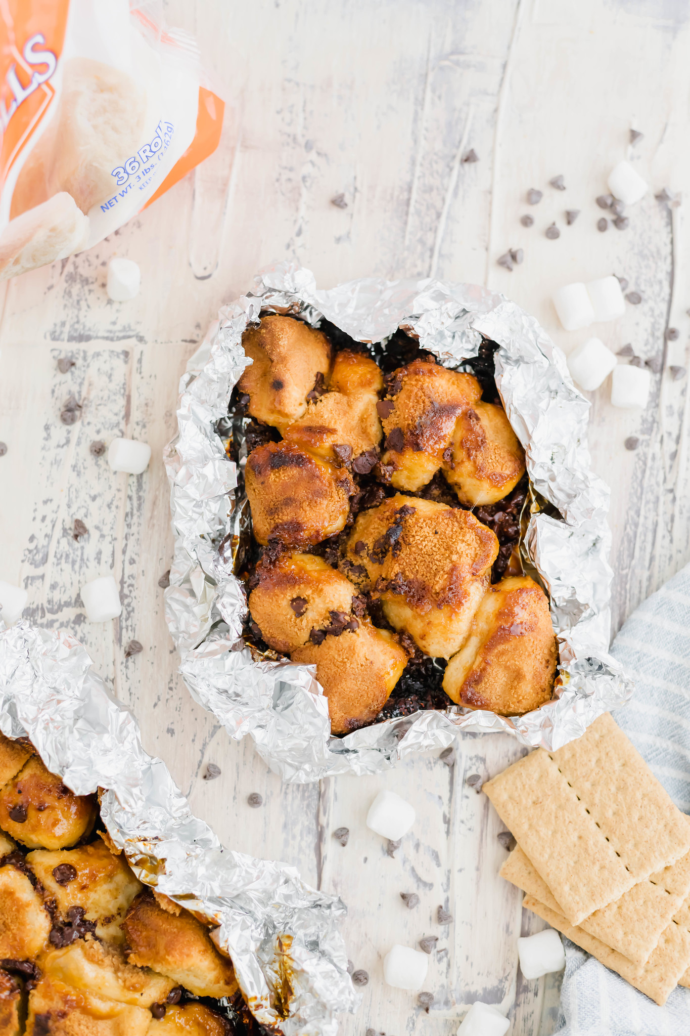 Summertime is upon us and this summer, we're firing up the grill for a super fun dessert featuring Rhodes Bake-N-Serv rolls. This Campfire S'mores Monkey Bread is super simple to make on the grill or in the oven for a fun spin on a summertime classic.