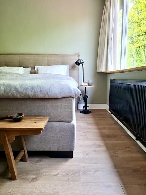 Beige bed met hoofdbord houten vloer zwarte radiator landelijke slaapkamer