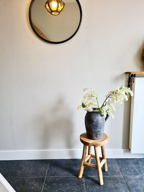 Landelijke grijze kruik op houten krukje ronde spiegel hal
