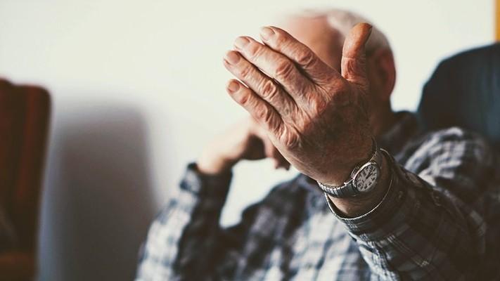 Elderly man holding up hand