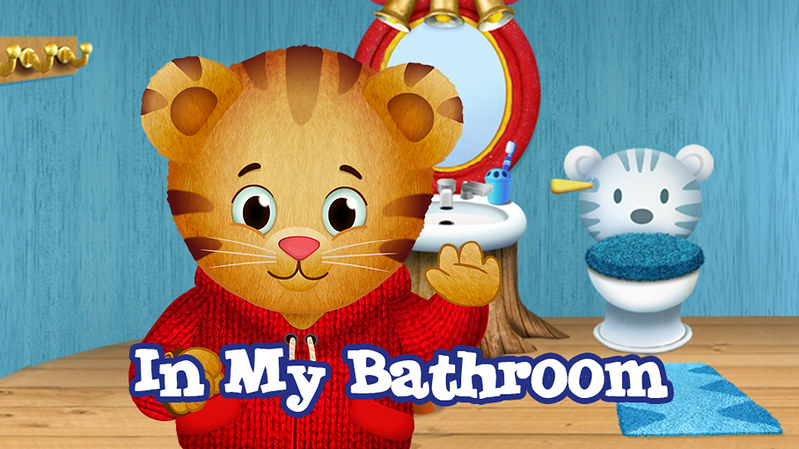 A cartoon tiger boy, in a cartoon bathroom. A goofy-fonted caption at the bottom of the image reads IN MY BATHROOM. Daniel is wearing a red cable-knit hoodie with large pockets. The toilet behind him has a be-carpeted lid, and is decorated to look like a feline. The implications of that decorative choice boggle the mind.
