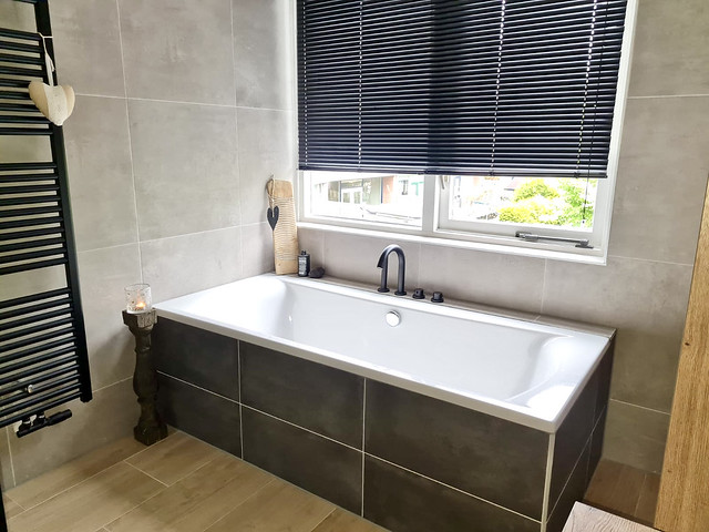 Landelijke badkamer bruine tegels bad zwarte luxaflex balusterkandelaar