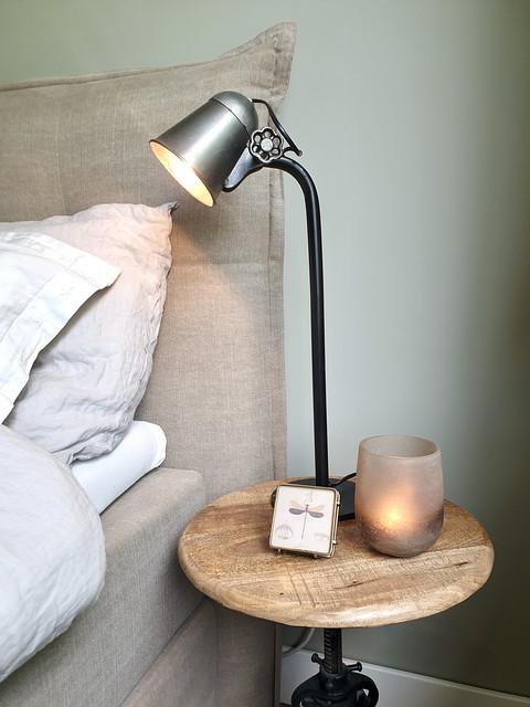 Beige gestoffeerd bed met hoofdbord linnen dekbedovertrek leeslamp op rond tafeltje naast bed