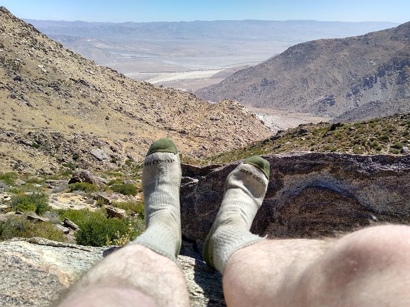 Me, taking a boot-off break and drying my socks with a view of Snow Creek and the Coachella Valley from the PCT