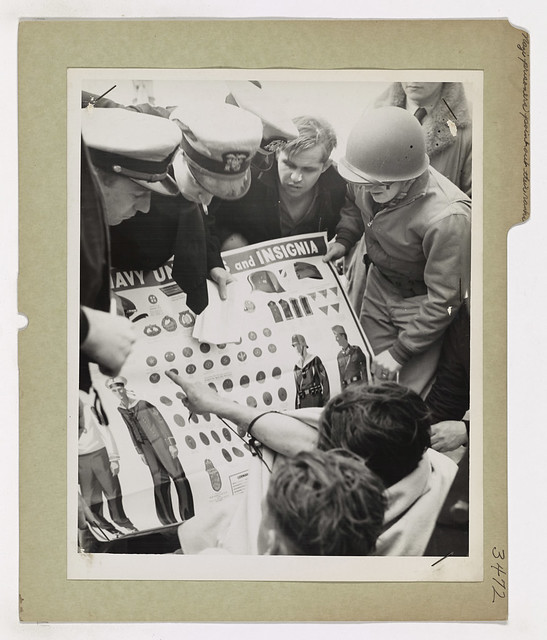 Rescued from the Atlantic after their submarine had been sunk by a Coast Guard combat cutter, German prisoners point out their ranks on a chart provided by their Coast Guard captors.