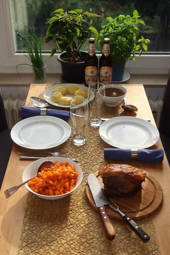 Schweinekrustenbraten mit viel Soße, Kartoffelklößen und Möhrengemüse (Tischbild)