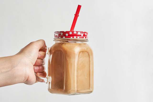 Female hand holds a glass of iced coffee drink