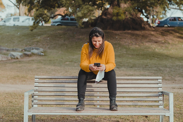 Horizontal shot of a woman sitting on a bench, using her cell phone. Holding a mouth cover in her hand while she takes in some fresh air. Concept of social distance during the coronavirus. Recreation in times of pandemic.