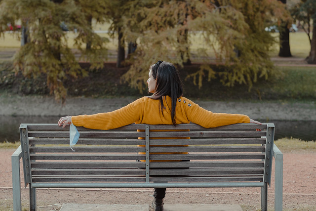 Horizontal shot of a woman sitting on a bench, her back, looking to the side. She holding in her hand a cover for her mouth while she takes some fresh air. Concept of social distance during the coronavirus. Recreation in times of pandemic.