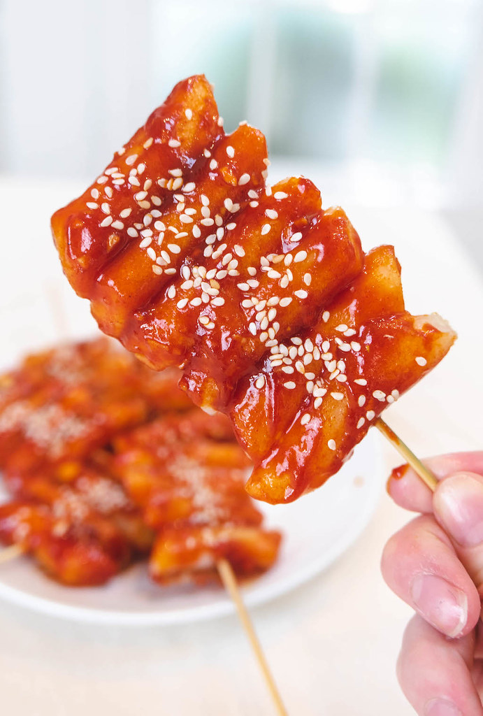 Holding a skewer next to a plate of tteokkochi.