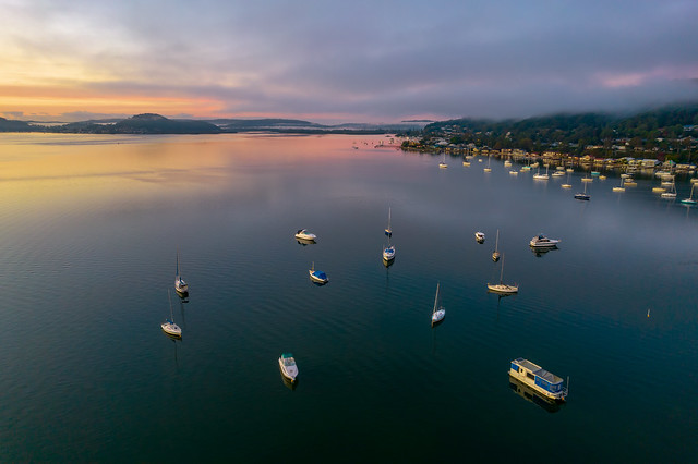 Sunrise waterscape with boats, light cloud and fog