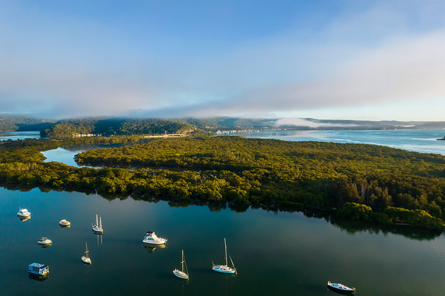 Early morning aerial waterscape with boats, light cloud and fog