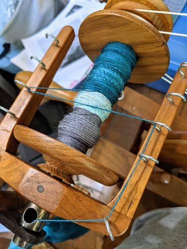 Bobbin and flyer array of Watson Martha spinning wheel with from back teal, light teal, grey handspun singles .  The wheel is made from Butternut wood.